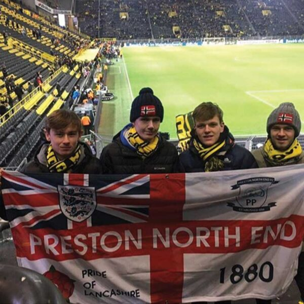 Four lads on the terrace holding Preston North End flag designed on Ultras Design website